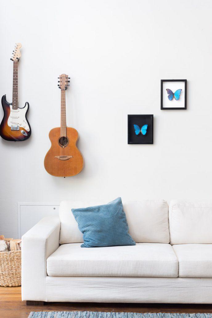 Tropiniai drugeliai rėmeliuose ant sienos su gitaromis